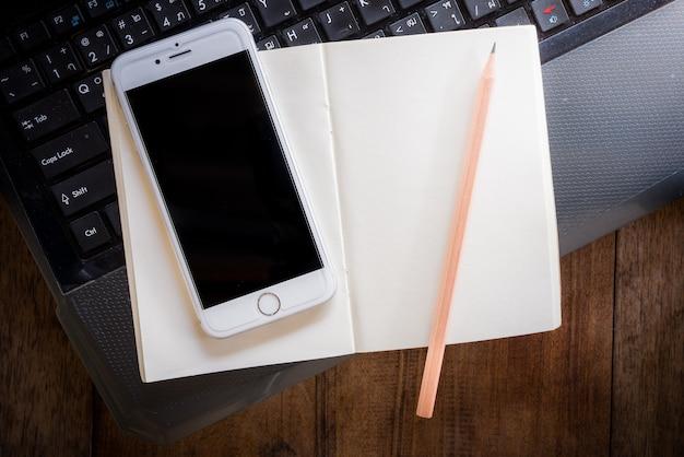 Leeg notitieboekje en smartphone met potlood op laptop
