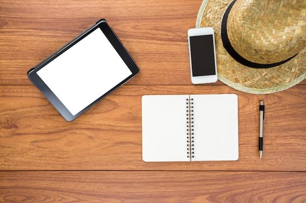 Leeg notitieboekje en tablet op houten achtergrond