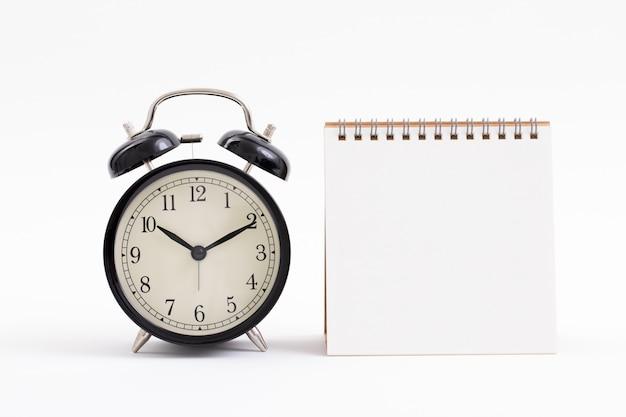 Leeg notitieboekje en uitstekende klok