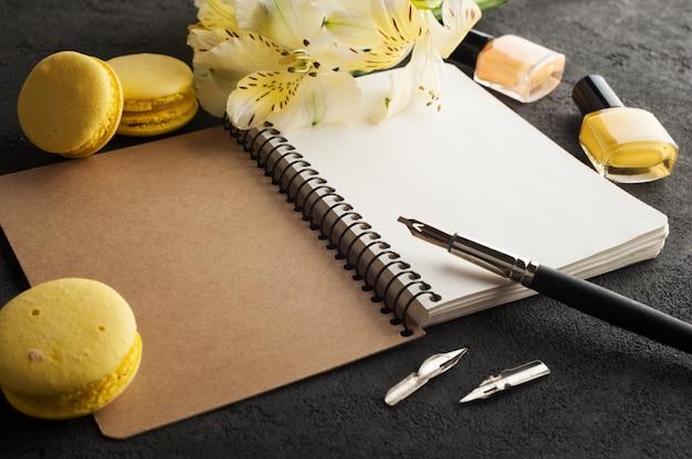 Leeg notitieboekje, gele makarons, pen