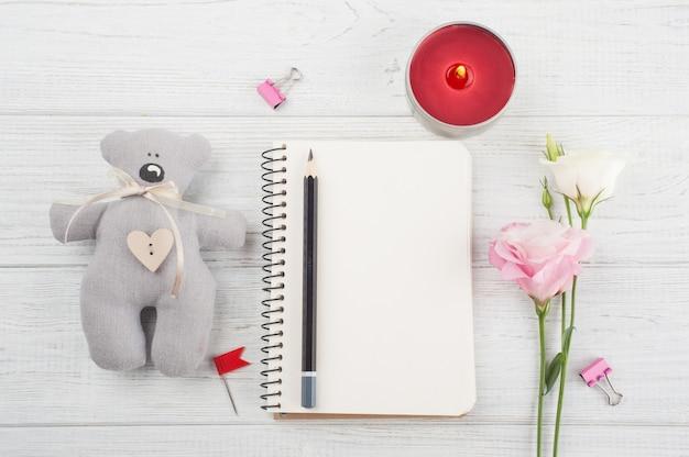 Leeg notitieboekje, kopje koffie, brandende kaars, bloemen