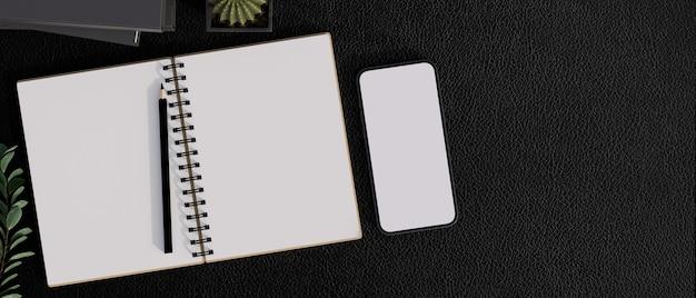 Leeg notitieboekje leeg scherm smartphone op zwarte werktafel met kamerplanten boeken en kopieer ruimte