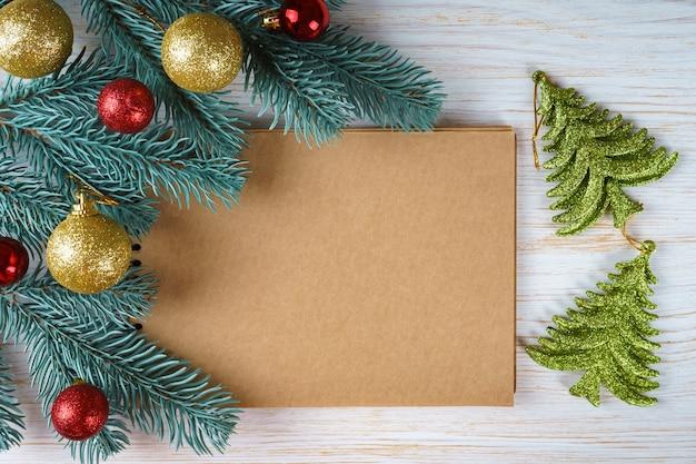Leeg notitieboekje met de takken van de kerstmisdecoratie kerstboom