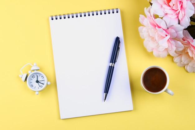 Leeg notitieboekje met een blauwe pen op een gele pastelkleurachtergrond. mock-up, lijst, sjabloon.