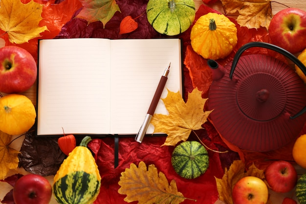 Leeg notitieboekje met esdoornblad, appelen en pompoenen