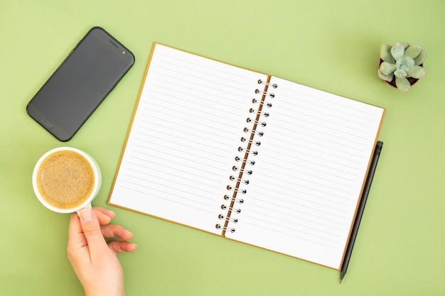 Leeg notitieboekje met lege pagina, potlood en hand die een koffiekop houden. tafelblad, werkruimte op groene achtergrond. creatief plat leggen.