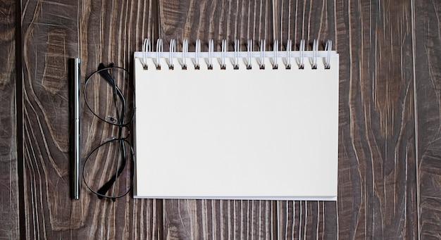 Leeg notitieboekje met pen, bril op de houten tafel, bedrijfsconcept