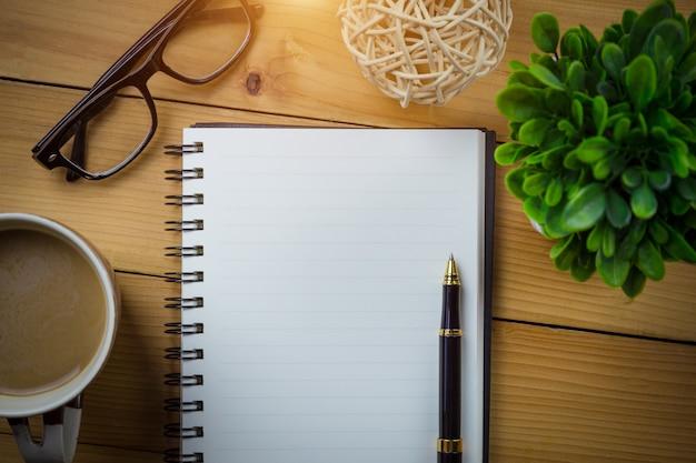 Leeg notitieboekje met pen en met glazen naast kop van koffie op houten lijst