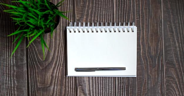 Leeg notitieboekje met pen op de houten tafel, bedrijfsconcept