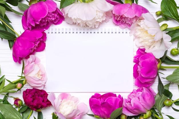 Leeg notitieboekje met plaats voor tekst en frame van pioenrozen bloemen op een witte houten achtergrond. uitzicht van boven.
