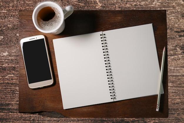 Leeg notitieboekje met potlood, smartphone en witte kop van koffie.