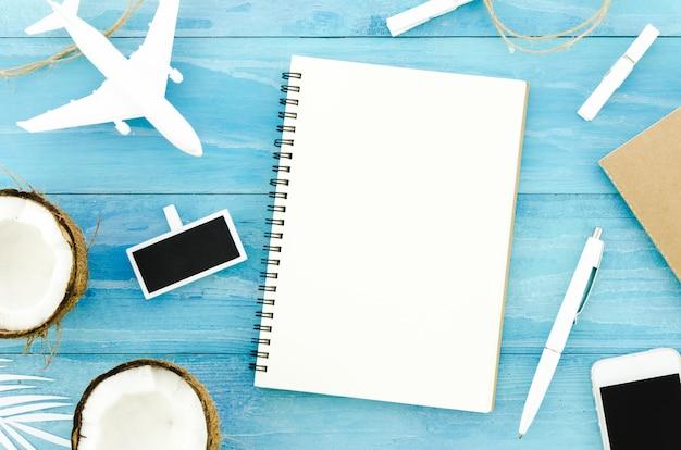 Leeg notitieboekje met stuk speelgoed vliegtuig en kokosnoten