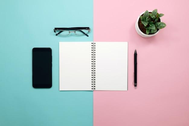 Leeg notitieboekje met telefoon, slimme telefoon, pen op vlakke desigachtergrond.