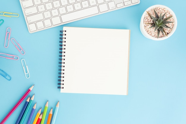 Leeg notitieboekje met toetsenbord en potlood op blauw