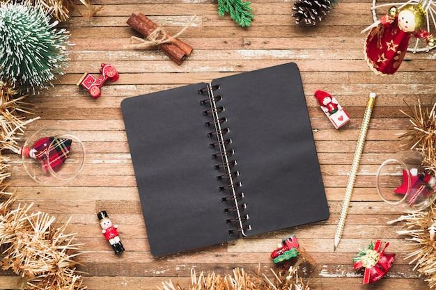 Leeg notitieboekje op hout met kerstmisornamenten