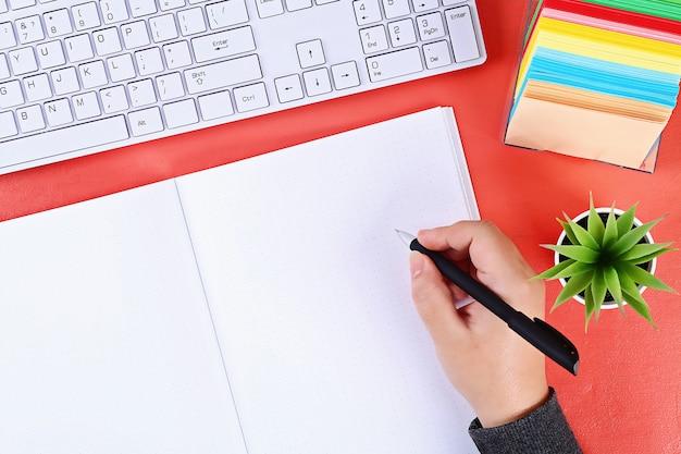Leeg notitieboekje op koraal, installatie, toetsenbord. bovenaanzicht, platliggend. mockup, copyspace.