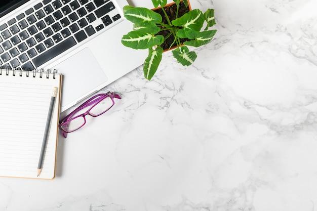 Leeg notitieboekje op laptop en kleine plant op marmeren tafel, bedrijfsconcept met bovenaanzicht