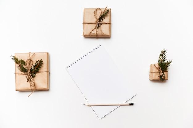 Leeg notitieboekje, potlood en geschenkdozen of cadeautjes verpakt in kraftpapier geïsoleerd op wit, bovenaanzicht.