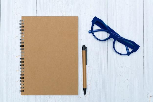 Leeg notitieboekjedocument en glazen met pen en bureaulevering, hoogste mening.