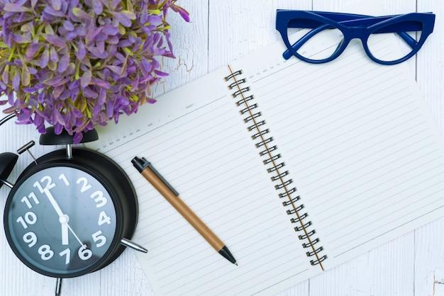 Leeg notitieboekjedocument en glazen met pen en bureaulevering