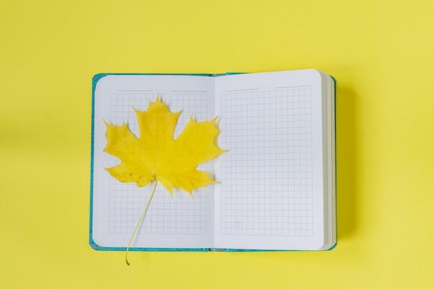 Leeg open notitieboekje met esdoornblad op geel. leeg dagboek