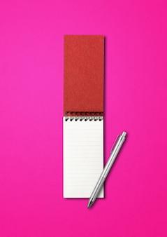 Leeg open spiraalvormig notitieboekje en penmodel dat op roze wordt geïsoleerd
