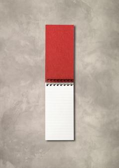 Leeg open spiraalvormig notitieboekjemodel dat op concrete achtergrond wordt geïsoleerd