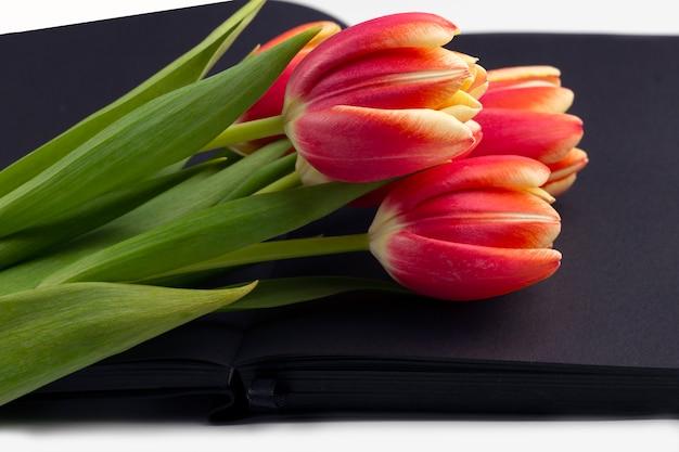 Leeg open zwart dagboek versierd met lente rode tulpen met ruimte voor tekst of belettering.