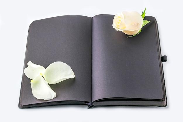 Leeg open zwart dagboek versierd met witte rozen met ruimte voor tekst of belettering.
