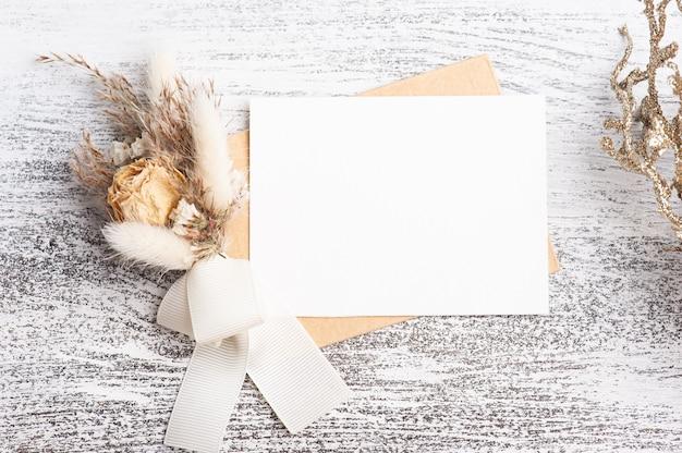 Leeg papier en kraft envelop met neutrale kleuren boeket droge bloemen. bruiloft mock up op witte tafel