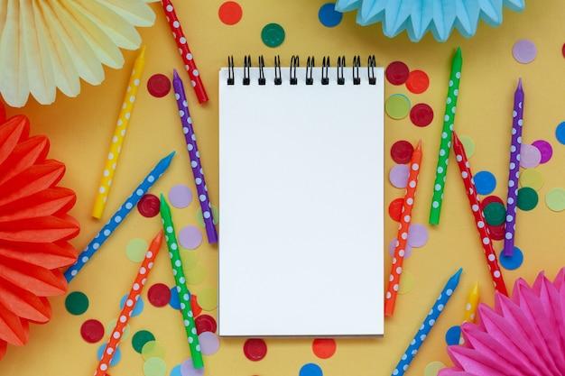Leeg papier leeg, feestelijke verjaardag kleurrijke kaarsen en papier fans op pastel gele verjaardag of feest