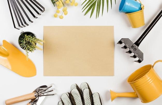 Leeg papier omringd door tuingereedschap