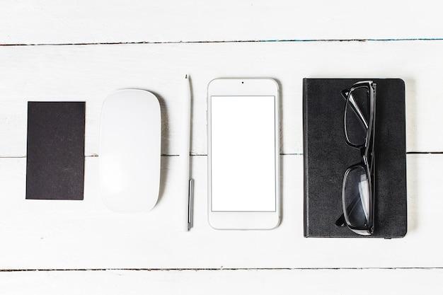 Leeg papierwerk sjabloon voor ontwerpers. responsieve design mockup op vintage houten achtergrond. papier, briefhoofd, koffiekopje, smartphone, potlood en koptelefoon op houten tafelachtergrond. bovenaanzicht.
