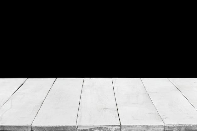 Leeg perspectief, witte houten planken of desktop tegen zwarte achtergrond. kan worden gebruikt als sjabloon en mockup voor weergave of montage van uw producten. sluiten, ruimte kopiëren