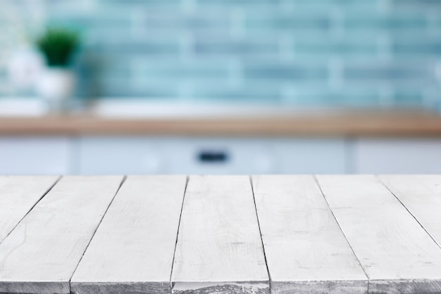 Leeg perspectief, witte houten planken of tafelblad tegen wazig keukeninterieur op achtergrond. kan worden gebruikt als sjabloon en mockup voor weergave of montage van uw producten. sluiten, ruimte kopiëren