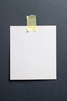 Leeg polaroid fotoframe met zachte schaduwen en geel plakband op zwarte ambachtelijke papier achtergrond