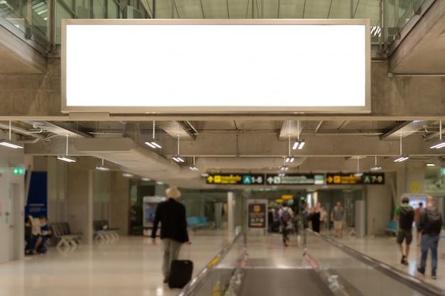 Leeg reclameaanplakbord bij bagageband in de luchthaven