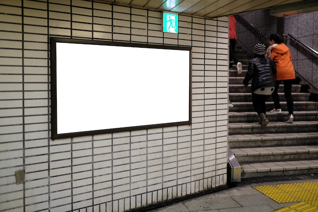 Leeg reclameaanplakbord en nooduitgangteken bij luchthaven