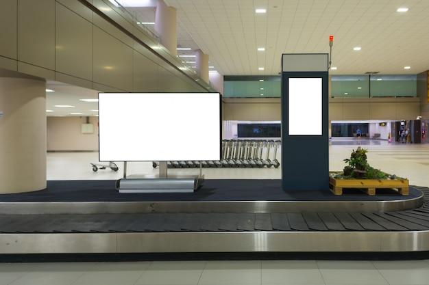 Leeg reclamebord bij bagageband op de luchthaven
