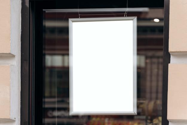 Leeg reclamebord klaar voor nieuwe advertentie die aan het raam van de winkel hangt. leeg reclamebordmodel voor reclameconcept