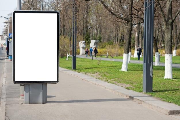 Leeg reclamebord of lightbox op groene stadsstraat met witte geïsoleerde background