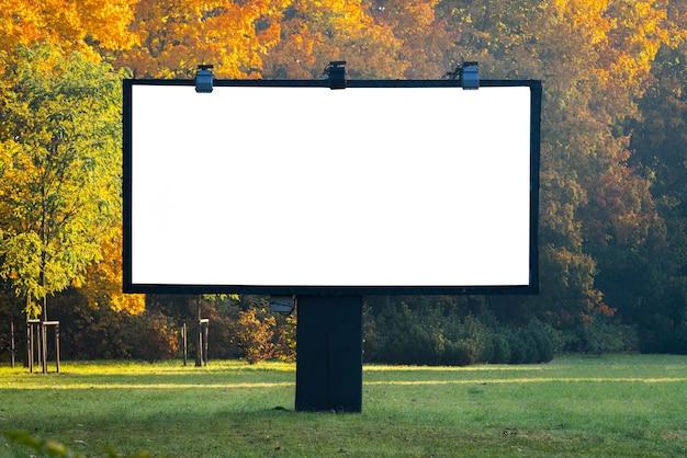 Leeg reclamebord omgeven door bos buiten aan de straatkant.