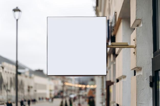 Leeg reclamebordmodel voor reclame. leeg reclamebord klaar voor nieuwe advertentie die aan het gebouw hangt met stadsstraatachtergrond