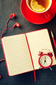 Leeg rood notitieboekje, computerlaptop, hoofdtelefoons en kop thee.