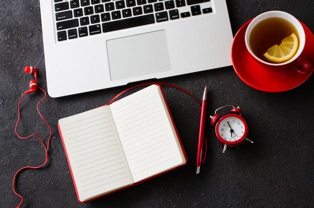 Leeg rood notitieboekje, computerlaptop, wekker, hoofdtelefoons en kop thee