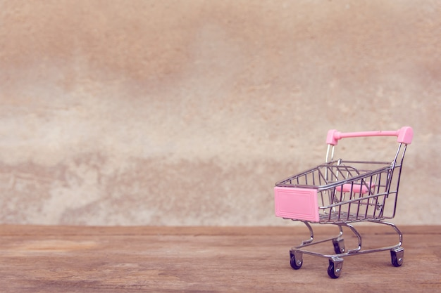 Leeg roze boodschappenwagentje op bruine houten lijst.
