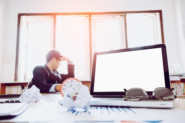 Leeg scherm laptop en kantoorapparatuur op bureau met onscherpe achtergrond van zakenman
