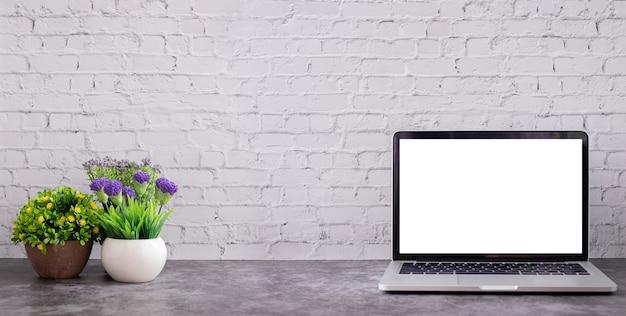 Leeg scherm laptop met bloempot op witte bakstenen muur textuur.