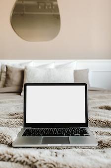 Leeg scherm laptop op bed met kussens voor beige muur