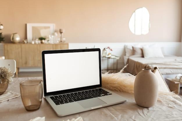 Leeg scherm laptop op tafel met prachtige decoraties. modern gezellig comfortabel huis woonkamer interieur.